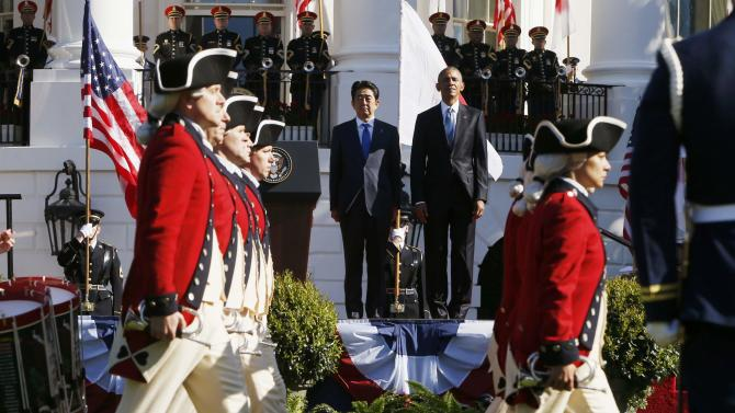 Members of the U.S. Army Old Guard Fife and Drum Corps march past Obama and Abe during during an official arrival ceremony for Japanese Prime Minister Abe at the White House in Washington