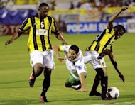 Al-Ahli's midfielder Taisir al-Jassam is fouled by Al-Ittihad's defenders Osama al-Harbi (L) and Ibrahim Hazazi (R) during their AFC Champions League first leg semi-final football match in the Saudi coastal city of Jeddah. Al-Ittihad won 1-0
