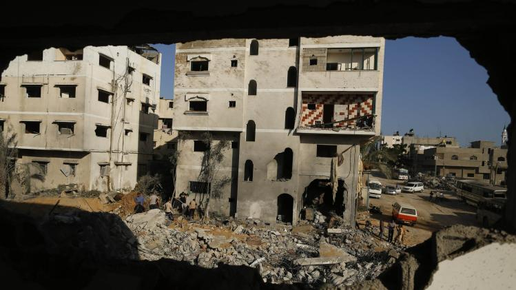 Palestinians inspect a house that witnesses said was destroyed during an Israeli air strike in Gaza City