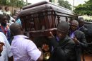 Pallbearers carry the coffin of late author Chinua Achebe at his funeral service, held at St. Philip's Anglican Church in Ogidi, Nigeria, Thursday, May 23, 2013. Writer Chinua Achebe shunned Nigeria?s corrupt politicians and twice turned down national honors, never fearing to criticizing those he felt ruined a country he once supported breaking away from. On Thursday, however, the lawmakers and the country?s elite came to him. Hundreds attended Achebe?s funeral among the rolling hills of his eastern Nigeria home, a service that saw even President Goodluck Jonathan literally hold up the writer?s books. The gold plaque on his coffin simply called him the ?eagle atop the Iroko tree? in his native Igbo language. (AP Photo/Sunday Alamba)