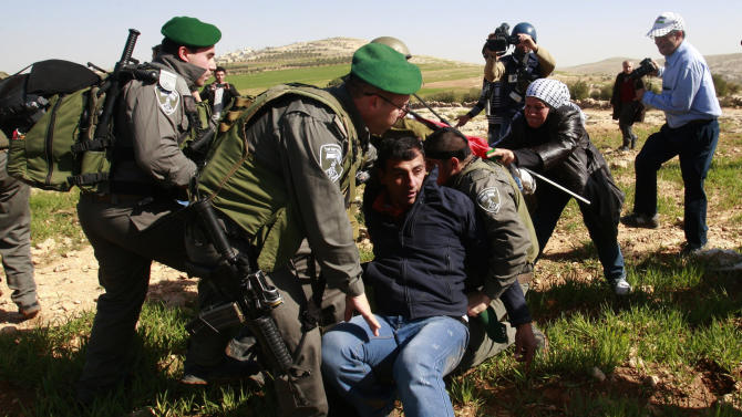 Israeli security arrests Palestinian activists in Yatta, south of the West Bank city of Hebron, Saturday, Feb. 9, 2013. Palestinian activists set up a tent village to protest the settlement building in the area. (AP Photo/Nasser Shiyoukhi)