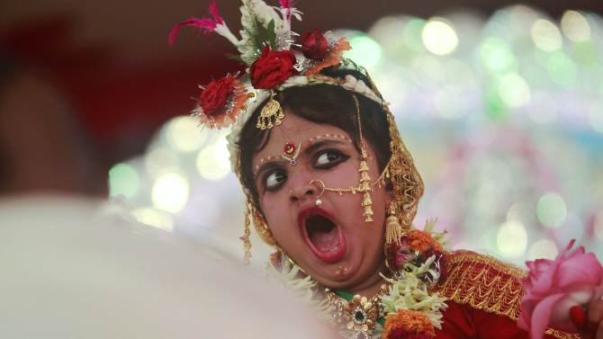 Girl, dressed as a Kumari, yawns while she is worshipped by a Hindu priest during the religious festival of Durga Puja in the northeastern Indian city of Agartala