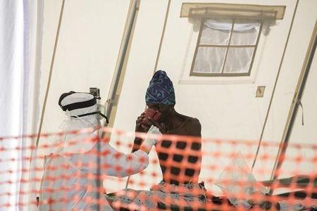British health worker Michelle Gundry treats a suspected Ebola patient inside a quarantine zone in a Red Cross facility in the town of Koidu
