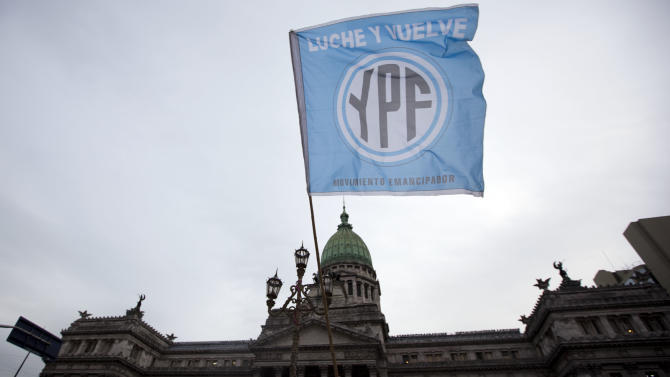 "A supporters of an oil nationalization bill proposed by Argentina's President Cristina Fernandez holds a flag reading in Spanish ""Fight and return YPF"" outside Congress as senators debate the bill in Buenos Aires, Argentina, Wednesday, April 25, 2012. Fernandez, who pushed forward a bill to renationalize the country's largest oil company, said the legislation put to congress would give Argentina a majority stake in oil and gas company YPF by taking control of 51 percent of its shares currently held by Spain's Repsol. (AP Photo/Natacha Pisarenko)"