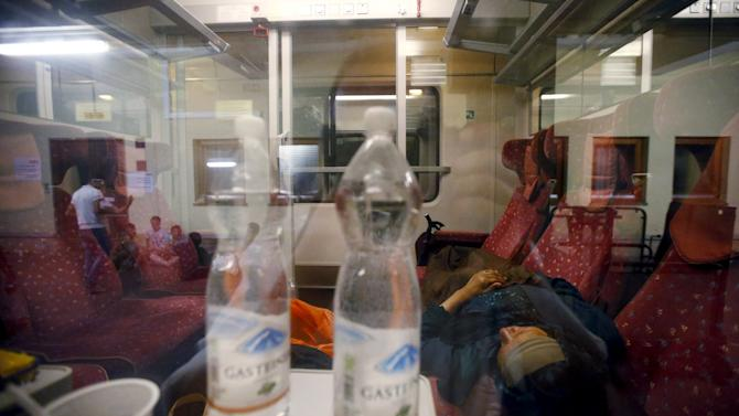 Woman believed to be a migrant sleeps in a train after arriving from Hungary at the railway station in Vienna, Austria