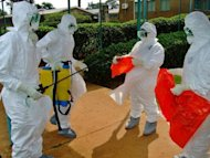 <p>World Health Organization officials wear protective gear as they prepare to enter Kagadi Hospital in Uganda's western Kibale district last week. Hillary Clinton will spend one night in Kampala, the Ugandan capital which has been hit for the first time by an Ebola outbreak that has already killed 15 people nationwide.</p>