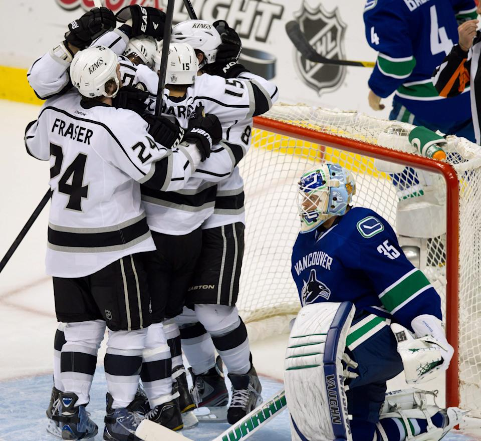 Los Angeles Kings' Brad Richardson is mobbed by his teammates after scoring against Vancouver Canucks' goalie Cory Schneider, right, during the third period of game 5 of an NHL Western Conference quarterfinal Stanley Cup playoff hockey series in Vancouver, British Columbia on Sunday April 22, 2012. (AP Photo/The Canadian Press, Darryl Dyck)