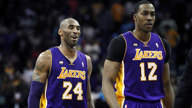 Los Angeles Lakers shooting guard Kobe Bryant (24) walks off the court during a timeout with center Dwight Howard (12) after scoring a basket late in the second half of an NBA basketball game against the New Orleans Hornets in New Orleans, Wednesday, March 6, 2013. The Lakers won 108-102. (AP Photo/Gerald Herbert)