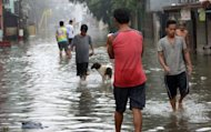 Residents are seen walking through a flooded street in Manila, on September 15. Surprise overnight monsoon rains, enhanced by the passage of Typhoon Sanba, caused flooding in the Philippine capital, forcing hundreds to flee their homes