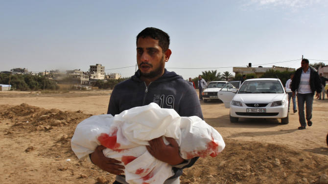Palestinian Yoused Abu Khoussa, carries the body of his year-and-a-half old son Iyad, during his funeral in Bureij Refugee Camp, central Gaza Strip, Sunday, Nov. 18, 2012. The baby boy was one of five Palestinian children killed in Israeli strikes on Sunday, according to a Gaza health official.(AP Photo/Adel Hana)