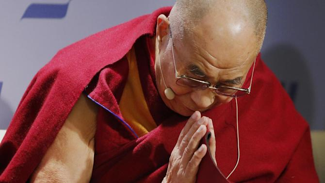 """Tibetan spiritual leader the Dalai Lama acknowledges the audience before speaking at an event entitled: """"Happiness, Free Enterprise, and Human Flourishing"""" Thursday, Feb. 20, 2014, at the American Enterprise Institute in Washington. (AP Photo/Charles Dharapak)"""