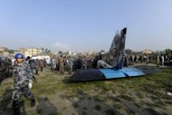 Onlookers and rescuers are seen near the wreckage of an Sita Air Dornier plane crash in Manohara, on the outskirts of Kathmandu on September 28, 2012. Nepal has a poor road network and large numbers of tourists, pilgrims and professional climbers often rely on the country&#39;s 16 domestic airlines and 49 airports to reach remote areas