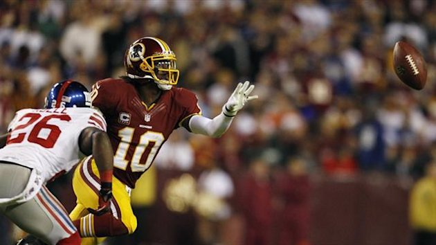 Washington Redskins quarterback Robert Griffin III flips the ball while pressured by the New York Giants Antrel Rolle (Reuters)
