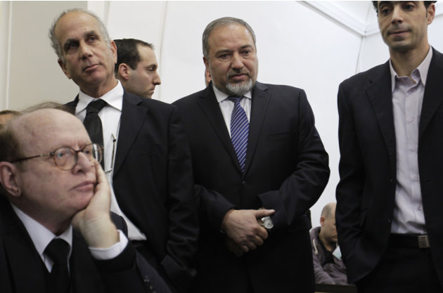 Israel's former hard-line Foreign Minister Avigdor Lieberman, second right, is seen with lawyers and aides as he arrives at a Jerusalem court for the opening hearing of his trial on charges of fraud a