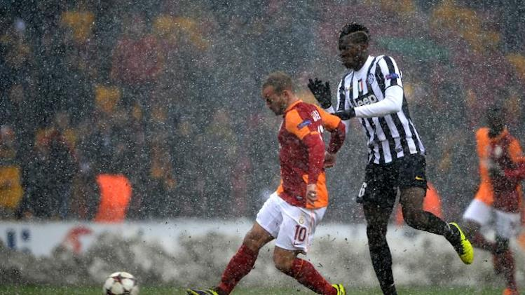 Galatasaray's Wesley Sneijder (L) fights for the ball with Juventus' Paul Pogba during their Champions League group B match on December 11, 2013, at Turk Telekom Arena in Istanbul