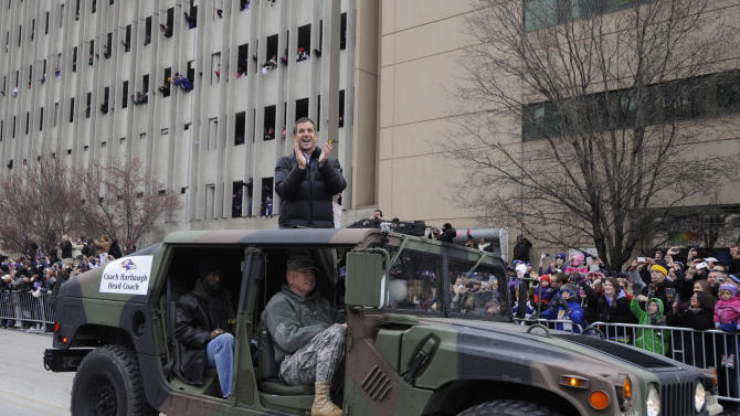Baltimore Ravens head coach John Harbaugh applauds fans while riding in a Humvee during the Ravens victory parade Tuesday, Feb. 5, 2013, in Baltimore. The Ravens defeated the San Francisco 49ers in NFL football's Super Bowl XLVII 34-31 on Sunday. (AP Photo/Gail Burton)