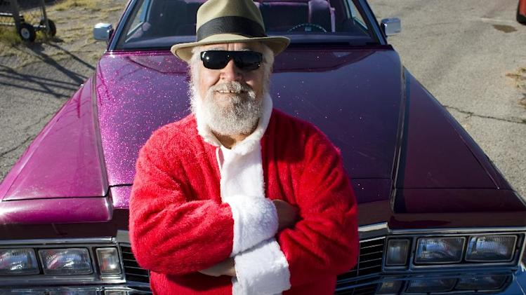 FILE - In this Dec. 15, 2008 file photo, Pete Martinez of Odessa, Texas, dressed as Pancho Claus, stands with a lowrider in central Odessa. (AP Photo/Houston Chronicle, Nick de la Torre) MANDATORY CREDIT