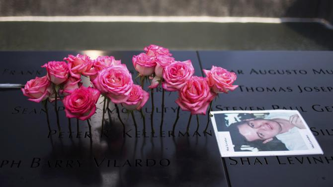 Roses are placed on the inscribed name of Peter Kellerman next to an image of Shai Levinhar along the North Pool during 9/11 Memorial ceremonies marking the 12th anniversary of the 9/11 attacks on the World Trade Center in New York