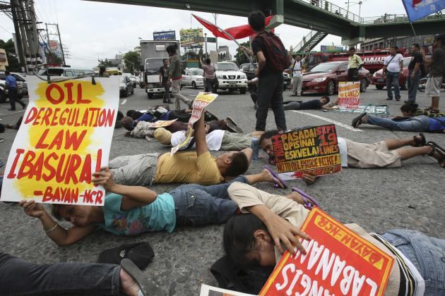 "Protesters lie prone on the pavement to do a ""planking,"" blocking briefly the traffic at a busy roundabout in Manila, Philippines, Monday, Sept. 19, 2011 to support calls for a nationwide ""transport h"