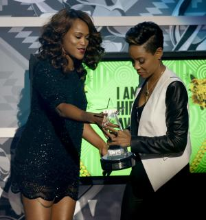 "Rapper Eve, left, presents rapper MC Lyte with the ""I Am Hip Hop Award"" during the BET Hip Hop Awards, Saturday, Sept. 28, 2013, in Atlanta. (AP Photo/David Goldman)"