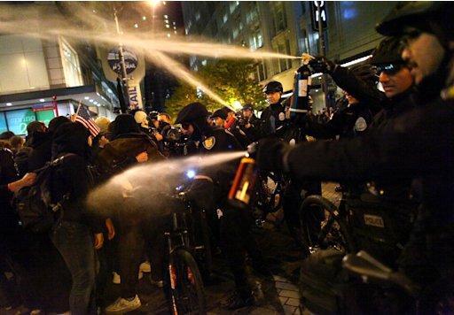Seattle Police officers deploy pepper spray into a crowd during an Occupy Seattle protest on Tuesday, Nov. 15, 2011 at Westlake Park in Seattle. Protesters gathered in the intersection of 5th Avenue and Pine Street after marching from their camp at Seattle Central Community College in support of Occupy Wall Street. Many refused to move from the intersection after being ordered by police. Police then began spraying pepper spray into the gathered crowd hitting dozens of people. (AP Photo/seattlepi.com, Joshua Trujillo)  MAGS OUT; NO SALES; SEATTLE TIMES OUT; TV OUT; MANDATORY CREDIT