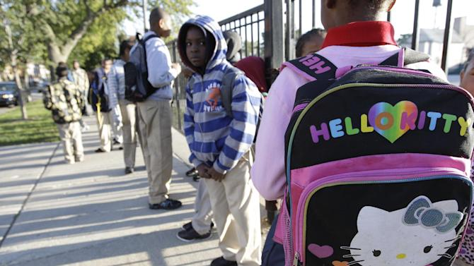 Students gather outside Benjamin E. Mays Academy , Wednesday morning, Sept. 19, 2012 in Chicago, after Chicago teachers voted to suspend their first strike in 25 years. Union delegates voted overwhelmingly Tuesday night to suspend the walkout after discussing a proposed contract settlement with the nation's third largest school district.  (AP Photo/M. Spencer Green)