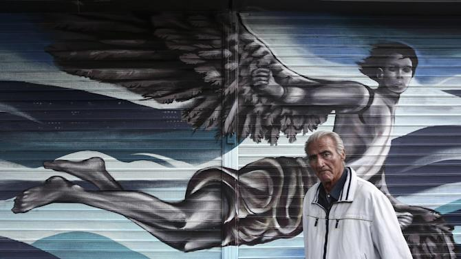 A man walks in front of a graffiti outside a shop in Athens, Greece, Thursday, May 28, 2015. Greece says it aims to clinch a deal with its creditors by Sunday, a development that would allow it to receive the desperately needed final installment of its international bailout plan and prevent a default. (AP Photo/Yorgos Karahalis)