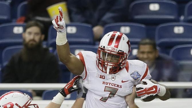 Rutgers running back Robert Martin (7) is lifted by offensive lineman Betim Bujari (55) after his touchdown during the second half of the Quick Lane Bowl NCAA college football game against North Carolina, Friday, Dec. 26, 2014, in Detroit. Rutgers defeated North Carolina 40-21