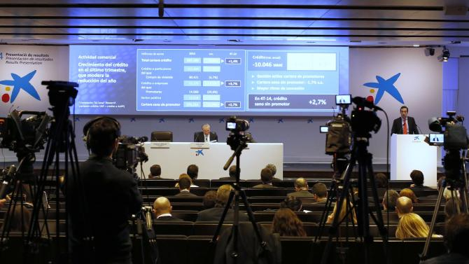 Cameras record CaixaBank's Chief Executive Officer Gonzalo Gortazar during a news conference where the bank presented its 2014 results at its headquarters in central Barcelona