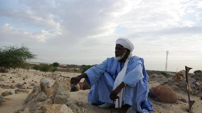 In this Oct. 19, 2012 photo, a man prays beside the remains of tombs of locally venerated Islamic saints, whose mausoleums were destroyed by Islamist group Ansar Dine, in Timbuktu, Mali. In recent months, al-Qaida and its allies have taken advantage of political instability within Mali to push out of their hiding place and into the towns, taking over an enormous territory which they are using to stock arms, train forces and prepare for global jihad. And as 2012 draws to a close and the world hesitates, delaying a military intervention, the extremists who seized control of the area earlier this year are preparing for a war they boast will be worse than the decade-old struggle in Afghanistan.(AP Photo)