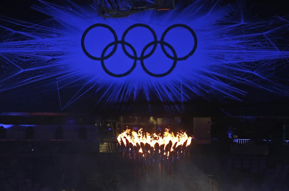 The Olympic Flame burns as the Olympic Rings stand illuminated during the Closing Ceremony at the 2012 Summer Olympics, Sunday, Aug. 12, 2012, in London. (AP Photo/Alastair Grant)