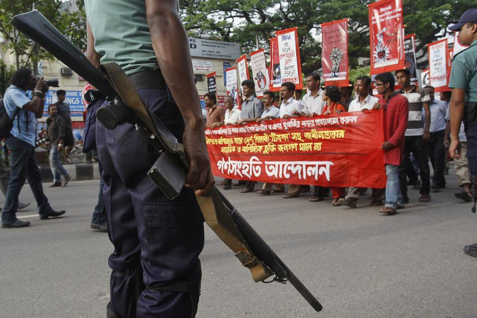 A police officer stands guard as protestors march in a rally against the visit of U.S. Secretary of State Hillary Clinton in Dhaka, Bangladesh, Friday, May 4, 2012. Clinton arrives Saturday for an official visit to the country. Banner reads 'Go back Hillary, we condemn her visit'. (AP Photo/Pavel Rahman)