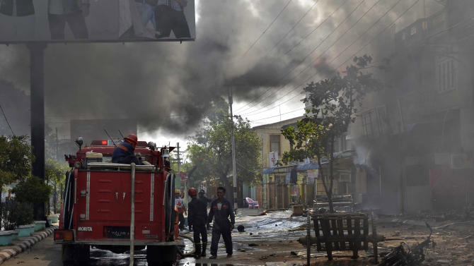 Myanmar firefighters battle fires in burning buildings following ethnic unrest between Buddhists and Muslims in Meikhtila, Mandalay division, about 550 kilometers (340 miles) north of Yangon, Myanmar, Friday, March 22, 2013. Black smoke and flames poured from the hulks of destroyed buildings in the central city of Meikhtila, where the unrest erupted Wednesday in the latest challenge to Myanmar's ever-precarious transition to democratic rule. (AP Photo/Khin Maung Win)