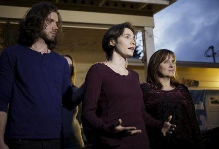 Amanda Knox talks to the press, flanked by her her fiance Colin Sutherland and mother Edda Mellas, outside her mother's home in Seattle, Washington