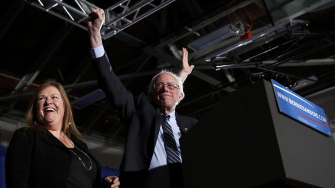 Democratic U.S. presidential candidate Sanders thrusts his fist in the air as he arrives with his wife Jane at his 2016 New Hampshire presidential primary night victory rally in Concord, New Hampshire