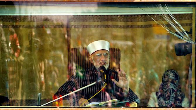 Pakistani Sunni Muslim cleric Tahir-ul-Qadri addresses his supporters from behind a bullet-proof glass during an anti-government rally in Islamabad, Pakistan, Wednesday, Jan. 16, 2013. Pakistan's leaders received a powerful one-two punch Tuesday as the Supreme Court ordered the arrest of the prime minister in a corruption case and the firebrand cleric led thousands of protesters another day of anti-government demonstrations in the capital.  (AP Photo/Anjum Naveed)