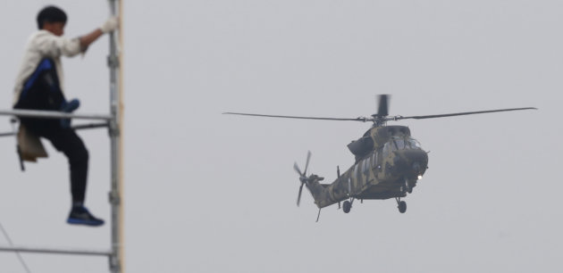 A Surion helicopter of the South Korean Army approaches to land as a worker prepares for a ceremony, during a photo call for the media at the Army Aviation School in Nonsan, south of Seoul