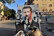 <p>A vandalised poster of Syrian President Bashar al-Assad lies in a trash container in the northern city of Aleppo on July 24. Human rights groups filed a complaint in Paris Wednesday to urge the judiciary to probe the alleged involvement of French firm Qosmos in supplying Syria's regime with surveillance equipment.</p>