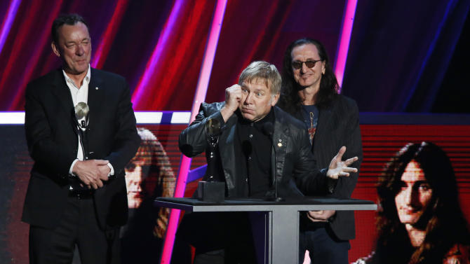 Alex Lifeson, center, Neil Peart, left, and Geddy Lee, right, of Rush accept their band's induction into the Rock and Roll Hall of Fame during the Rock and Roll Hall of Fame Induction Ceremony at the Nokia Theatre on Thursday, April 18, 2013 in Los Angeles. (Photo by Danny Moloshok/Invision/AP)