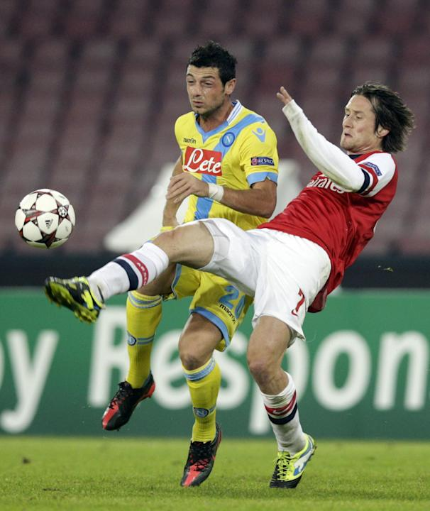 Napoli midfielder Blerim Dzemaili of Switzerland, left, and Arsenal's Tomas Rosicky fight for the ball during a Champions League, group F soccer match, at the Naples San Paolo stadium, Italy, Wedn