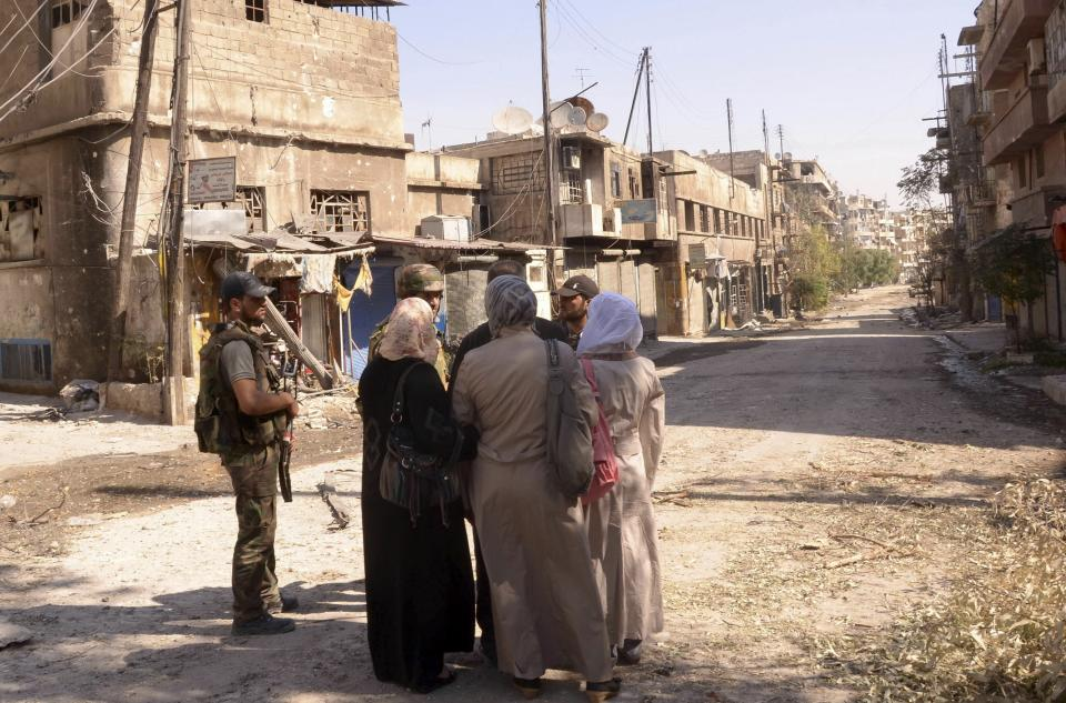 This photo released by the Syrian official news agency SANA, shows Syrian government forces speaking with Syrian women as they patrol the damaged area of the al-Arqoub district in Aleppo, Syria, Tuesday, Sept. 25, 2012. (AP Photo/SANA)
