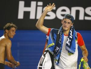 Bernard Tomic of Australia waves to the crowd after retiring from his men's singles match against Rafael Nadal of Spain at the Australian Open 2014 tennis tournament in Melbourne