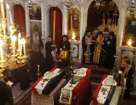 Clerics and other people attend the funeral of three men at Catholic Patriarchate in Damascus