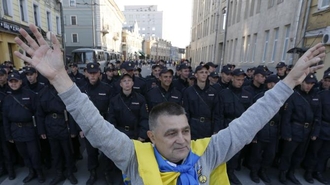 A man with a Ukrainian flag on his shoulders stands near a riot police line standing guard during an anti-war rally in Moscow