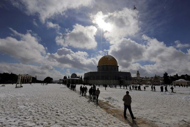 People walk in front of the Dome of the Rock in the compound known to Muslims as Noble Sanctuary and to Jews as Temple Mount, in Jerusalem's Old City following a snowstorm