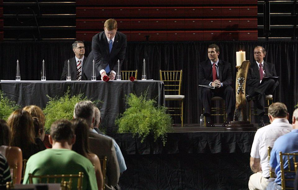 James Fowler,  places a rose beside a candle in honor of one of the six University of Alabama students who were killed during the April 27, 2011, tornado that ripped through Tuscaloosa, at a memorial service hosted in Foster Auditorium, Friday, Aug. 5, 2011. (AP Photo/The Tuscaloosa News, Michelle Lepianka Carter)