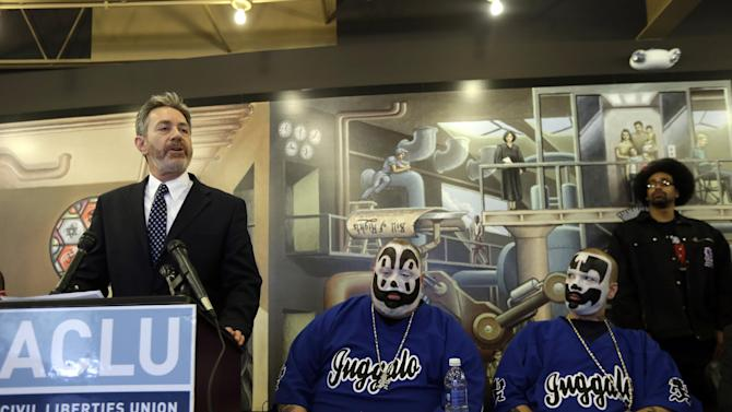 Michael J. Steinberg, legal director for the ACLU of Michigan addresses the media as Joseph Bruce aka Violent J, center, and Joseph Utsler aka Shaggy 2 Dope, members of the Insane Clown Posse listen in Detroit, Wednesday, Jan. 8, 2014. The rap metal group sued the U.S. Justice Department on Wednesday over a 2011 FBI report that describes the duo's devoted fans, the Juggalos, as a dangerous gang, saying the designation has tarnished their fans' reputations and hurt business. The American Civil Liberties Union filed the lawsuit in Detroit federal court on behalf of the group's two members. (AP Photo/Carlos Osorio)