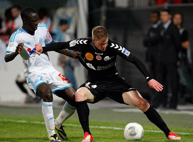 Stade de Reims' forward Gaetan Charbonnier, right, challenges for the ball with Marseille's French defender Benjamin Mendy during their League One soccer match, at the Velodrome Stadium, in Marseille,