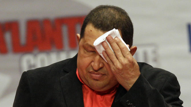 FILE - In this Thursday Feb. 23, 2012 file photo, Venezuela's President Hugo Chavez wipes his forehead as he attends a concert in his honor at the Teresa Carreno Theater in Caracas, Venezuela. Throughout his presidency, Chavez has relied on his vigor and endurance: playing baseball and speaking for hours at a stretch. Now Chavez finds himself ailing as he heads into a re-election campaign against Henrique Capriles, a 39-year-old state governor who represents a younger and more energetic option, said Diego Moya-Ocampos, an analyst with the London-based consulting firm IHS Global Insight. (AP Photo/Fernando Llano, File)