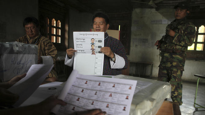 A polling official in traditional attire displays for other officials a document with photographs of candidates at a polling center on the eve of polling to the upper house National Council in Samdrup Jonkhar, Bhutan, Monday, April 22, 2013. The small Himalayan country of Bhutan ended more than a century of absolute monarchy by holding its first parliamentary elections in 2008. (AP Photo/Anupam Nath)